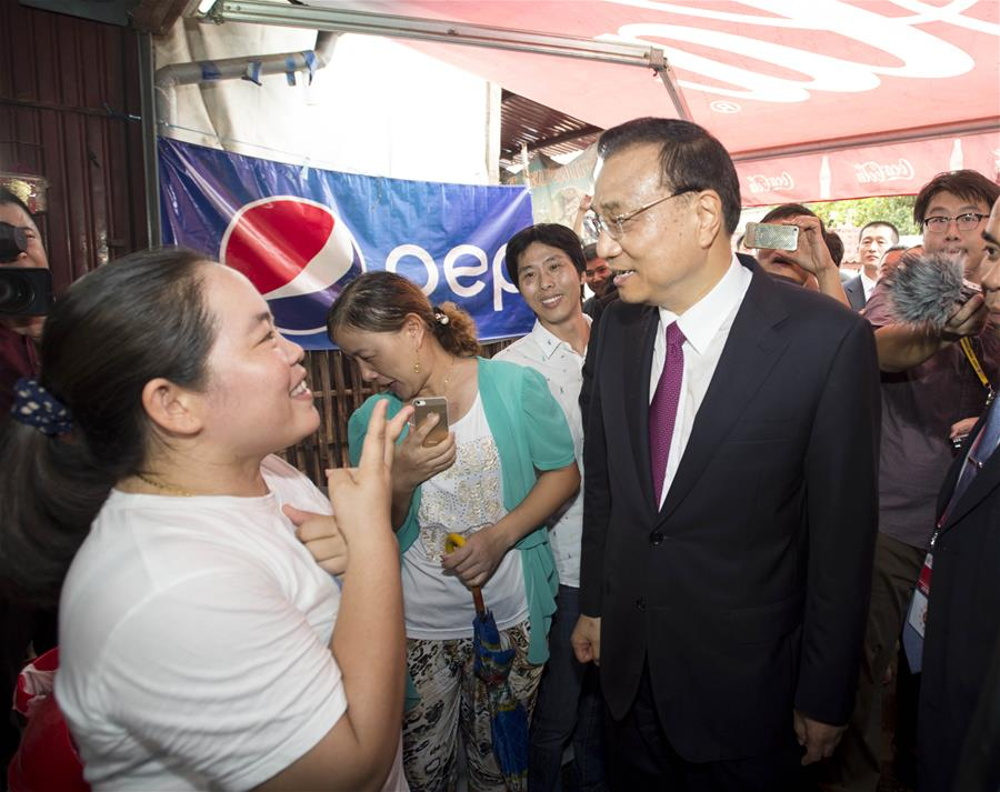 Chinese Premier Li Keqiang (R, front) talks to a woman as he walks into a local shop in Vientiane, Laos, Sept. 9, 2016.(Xinhua/Wang Ye)