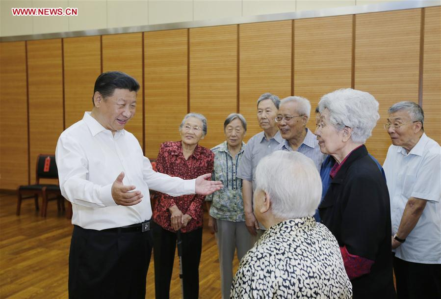 Chinese President Xi Jinping (1st L) talks to elder teachers during an inspection visit to Beijing Bayi School before the upcoming national Teacher