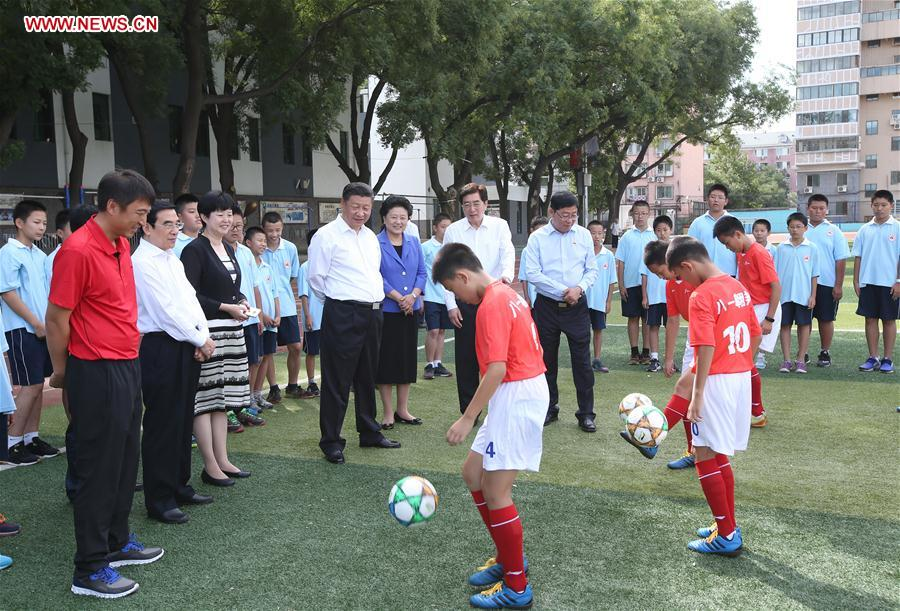 Chinese President Xi Jinping watches a football training session during an inspection visit to Beijing Bayi School before the upcoming national Teacher