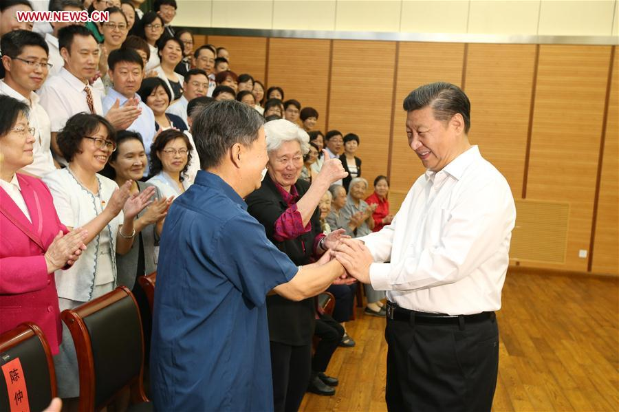 Chinese President Xi Jinping (1st R) shakes hands with representatives of teachers and students during an inspection visit to Beijing Bayi School before the upcoming national Teacher