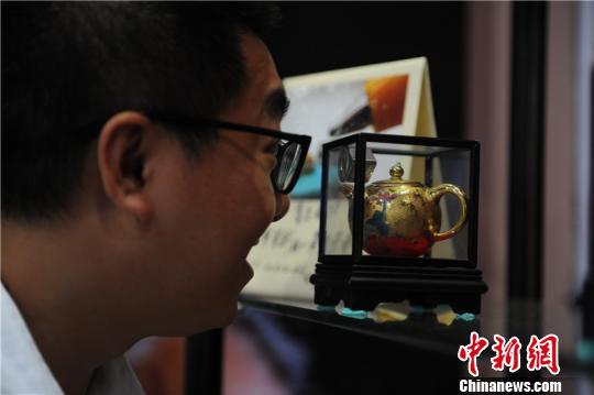 第六届中国(贵州)国际酒类博览会酒类产品衍生馆内,微雕大师陈逢显作品吸引民众观看。