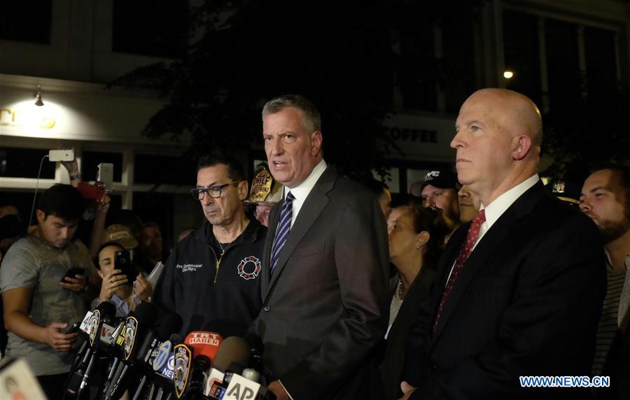 New York City Mayor Bill de Blasio (front, C) gives a news conference as New York Police Department Commissioner James O
