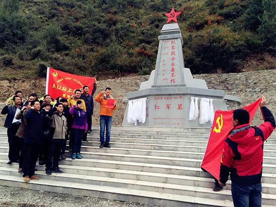 采访团成员在红军墓前重温入党誓词。