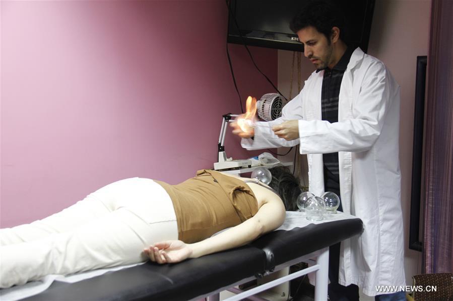 يعالج مشرف المركز أسامة حبيب الله المريض بعلاج الطب الصيني. (صورة شينخوا)