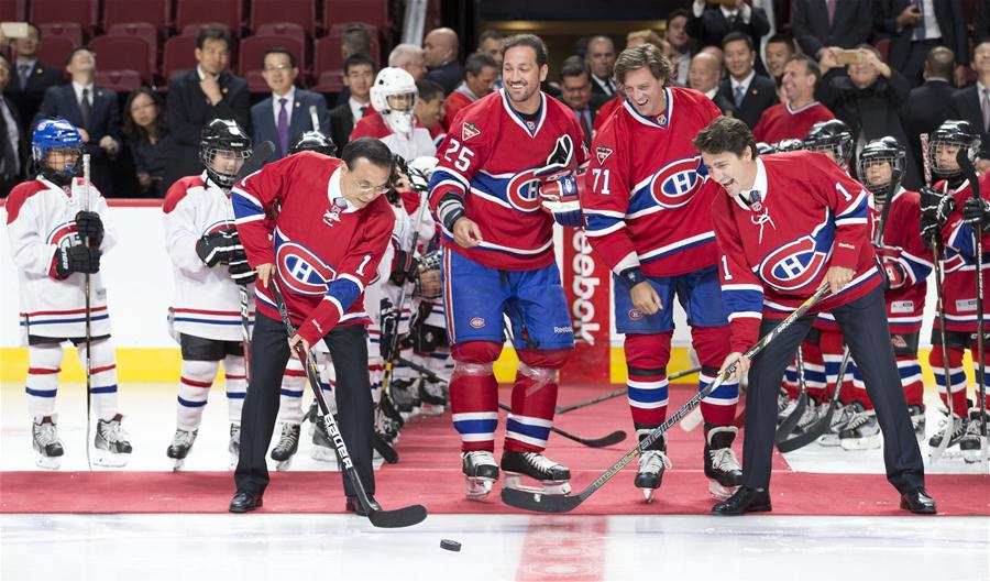 Chinese Premier Li Keqiang and his Canadian counterpart, Justin Trudeau, drop the ceremonial first puck for a training game of young players of Chinese origin as they visit Bell Center of renowned Canadian ice hockey team Montreal Canadiens in Montreal, Canada, Sept. 23, 2016. (Xinhua/Huang Jingwen)