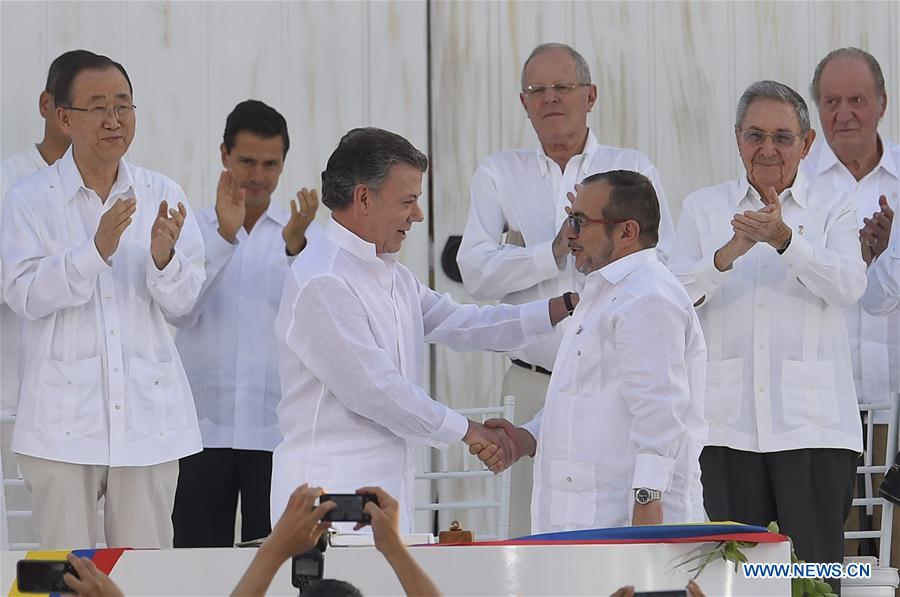 Image provided by the Colombian Presidency shows Colombian President Juan Manuel Santos (L Front) shaking hands with Commander in Chief of the Revolutionary Armed Forces of Colombia (FARC) Timoleon Jimenez during the signing ceremony of the final peace agreement between the Colombian government and FARC, in Cartagena, Colombia, Sept. 26, 2016. Juan Manuel Santos and Timoleon Jimenez Monday afternoon signed a historic peace deal in Cartagena, ending a 52-year conflict. (Xinhua/Juan Pablo Bello/Colombian Presidency)