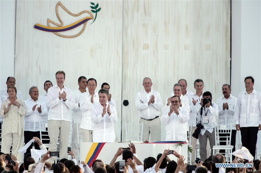 Colombian President Juan Manuel Santos and Commander in Chief of the Revolutionary Armed Forces of Colombia (FARC) Timoleon Jimenez attend the signing ceremony of the final peace agreement between the Colombian government and the FARC, in Cartagena, Colombia, Sept. 26, 2016. Juan Manuel Santos and Timoleon Jimenez signed a historic peace deal Monday afternoon in Cartagena, ending a 52-year conflict. (Xinhua/Jhon Paz)