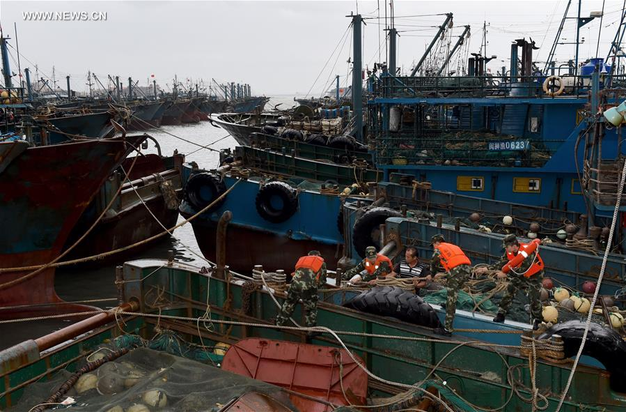 Soldiers help fishermen strengthen fishing boats at a port in Shishi, southeast China