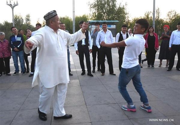 ييلي، شينجيانغ 27 سبتمبر2016 (شينخوا) في الصورة الملتقطة 26 سبتمبر 2016، أصدقاء وأهل زوجين يرقصون رقصات تقليدية للتهنئة في حفلة زفاف أقيمت على شاطئ نهر ييلي في منطقة شينجيانغ الويغورية ذاتية الحكم بشمال غربي الصين.