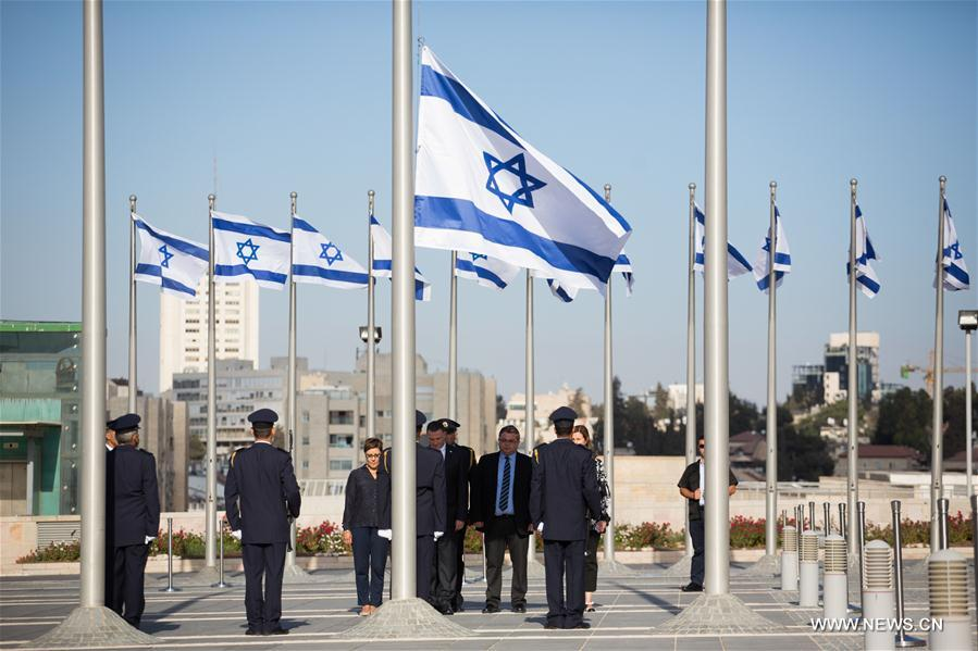 Members of Knesset Honor Guard lower the Israeli flag at half-mast during a ceremony in memory of former Israeli President Shimon Peres at the Knesset, the Israeli parliament in Jerusalem, Sept. 28, 2016. Israel