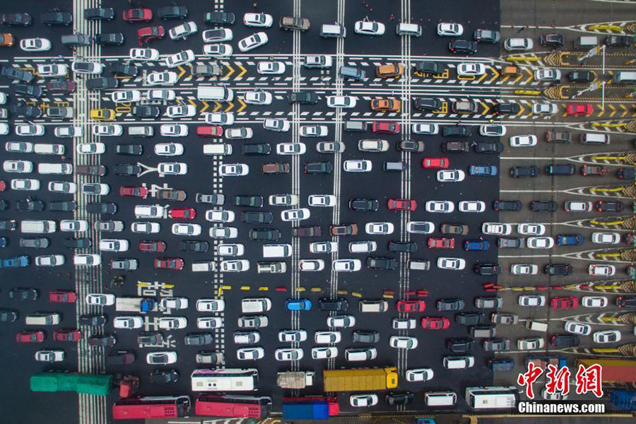 In this aerial view, masses of vehicles queue up to pass through a toll station on an expressway during the National Day holiday travel rush in Nanjing city, East China
