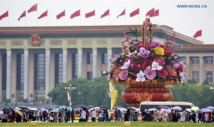 Tourists carrying umbrellas visit the Tian