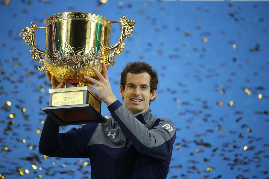 Andy Murray of Britain holds up his champion trophy during the awarding ceremony for the men
