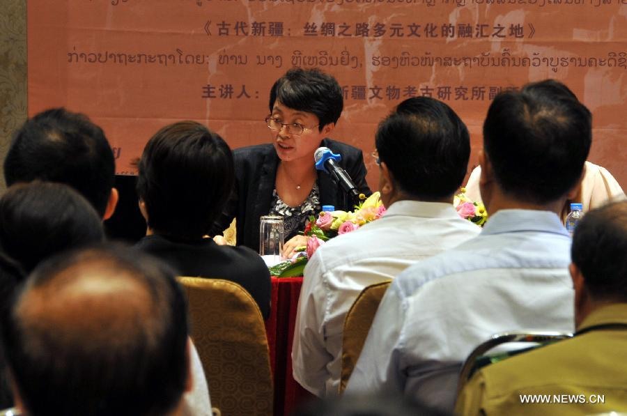 "Li Wenying (back), deputy director of Xinjiang Institute of Cultural Relics and Archaeology, speaks during a lecture ""Discovering the mystery of Xinjiang"" in Vientiane, Laos, Oct. 10, 2016. A lecture to introduce the cultural features of China"
