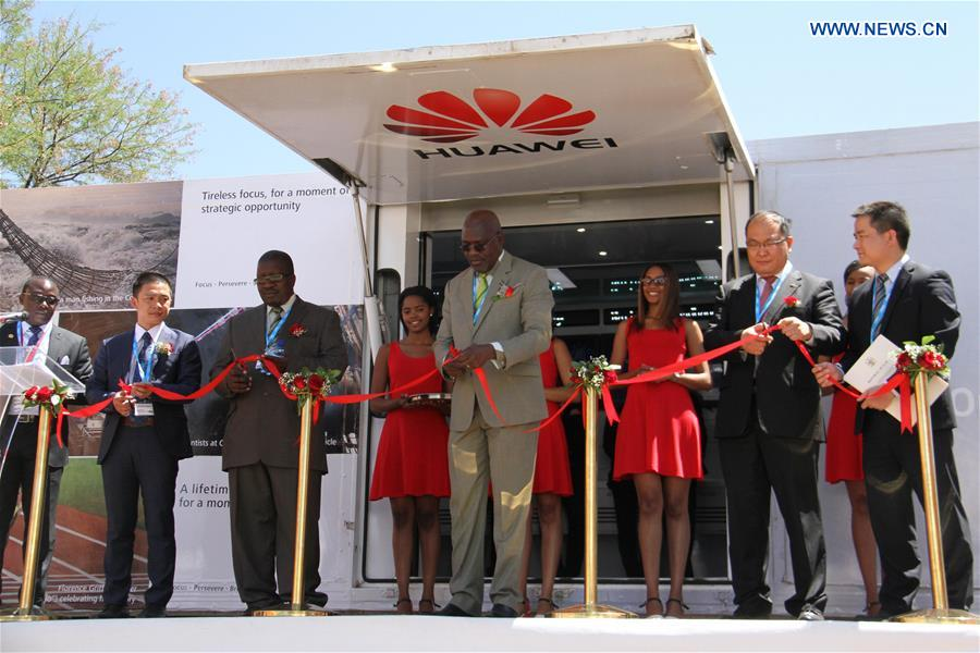 Namibian information minister Tjekero Tweya (C) cuts the ribbon for Huawei Demo Truck during the official opening of the 2016 ICT summit, in Windhoek, Namibia, on Oct. 10, 2016. China