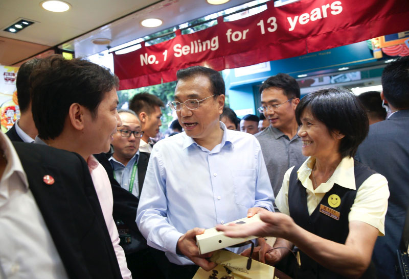 Chinese Premier Li Keqiang talks with owners of a dessert shop at Rua da Cunha, an ancient business street in Macao on October 11, 2016. He visited several shops on the pedestrian street, bought a box of egg tarts, a box of walnut cakes and a postcard. Li also posed for photos with local residents and tourists. [Photo: gov.cn]