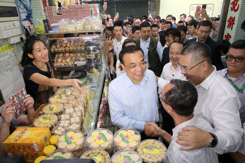 Chinese Premier Li Keqiang talks with an owner of a dessert shop at Rua da Cunha, an ancient business street in Macao. He visited several shops on the pedestrian street, bought a box of egg tarts, a box of walnut cakes and a postcard. Li also posed for photos with local residents and tourists. [Photo: gov.cn]