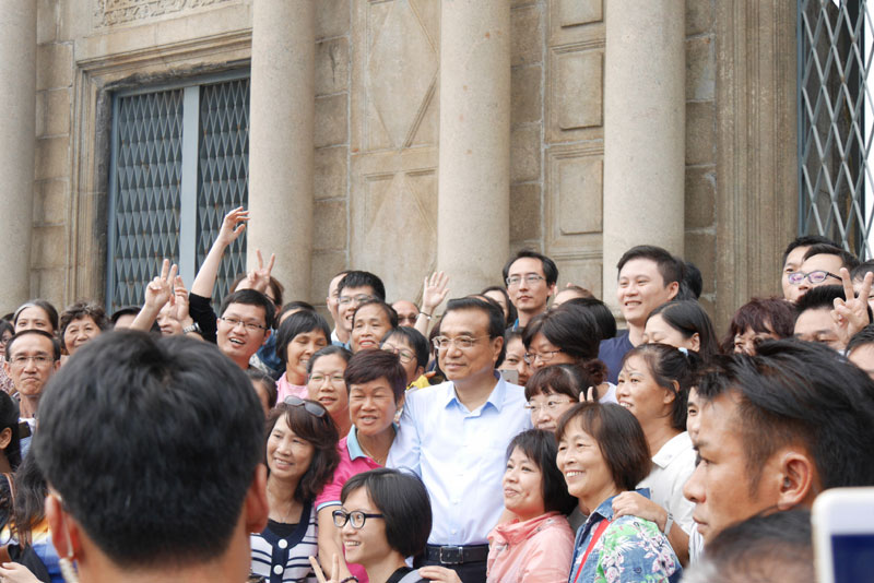 Li Keqiang poses for photos with local residents and tourists in front of the ruins of St. Paul, the city