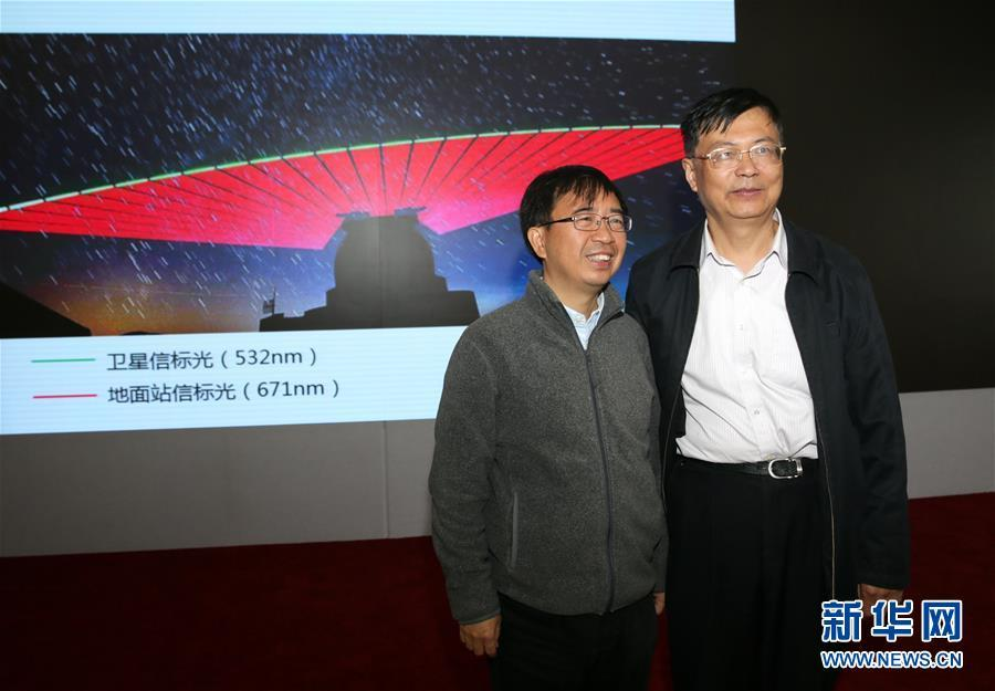 Pan Jianwei (L), the leading scientist in China's Quantum Science Satellite project, poses with Wang Jianyu, the deputy director of the project, in front of an image showing the transmissions between Quantum Science Satellite Mozi and a ground station during a press conference in Beijing, Oct. 12, 2016. It