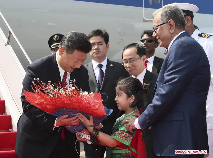 Chinese President Xi Jinping (1st L) accepts a bouquet upon his arrival at the airport in Dhaka, Bangladesh, Oct. 14, 2016. Xi Jinping arrived here Friday for a state visit. (Xinhua/Lan Hongguang)