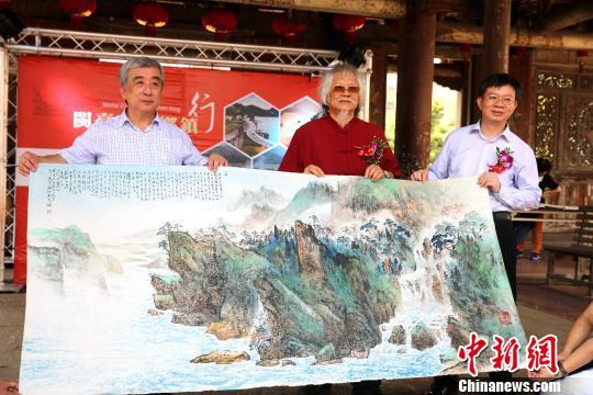 台湾著名画家王太田(中)与台湾导报社长林文雄(左)向海峡之声广播电台副总编郭红斌赠画。