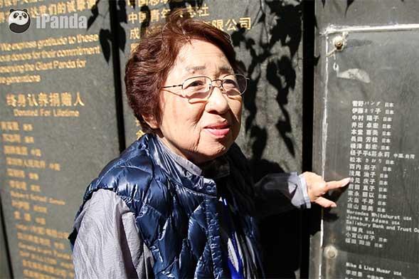 """铃见庆子在""""认养人纪念墙""""上指着自己的名字(尹忠旺 摄)"""