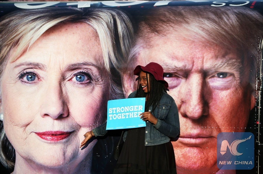 A girl poses for photos with Hillary Clinton and Donald Trump posters at Hofstra University in New York, the United States on Sept. 26, 2016. (Xinhua Photo)