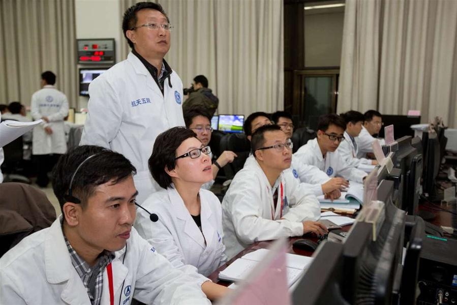 Staff members work before the Shenzhou-11 manned spacecraft