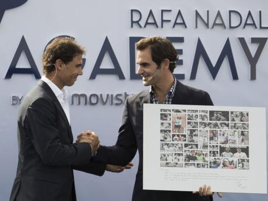 Rafa Nadal presents Roger Federer with a framed picture of their many duels down the years at the opening of his academy on Thursday.
