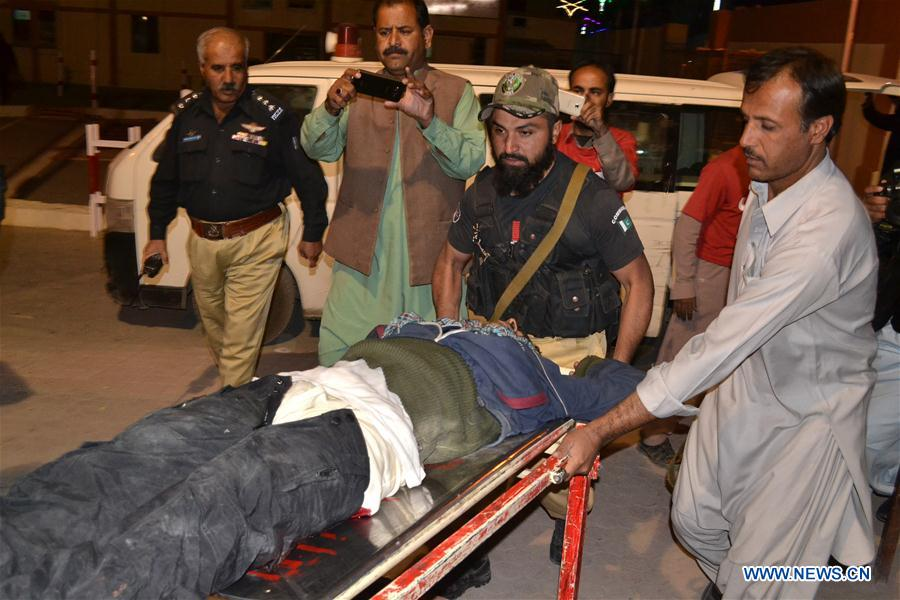 People transfer an injured police trainee to a hospital in southwest Pakistan