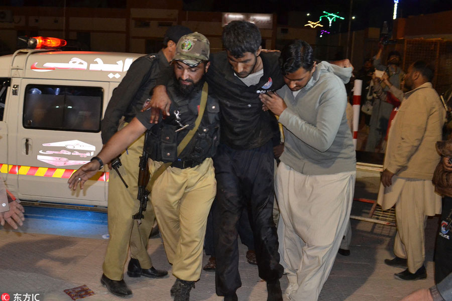 A Pakistani volunteer and a police officer rush an injured person to a hospital in Quetta, Pakistan, Oct 24, 2016. [Photo/IC]