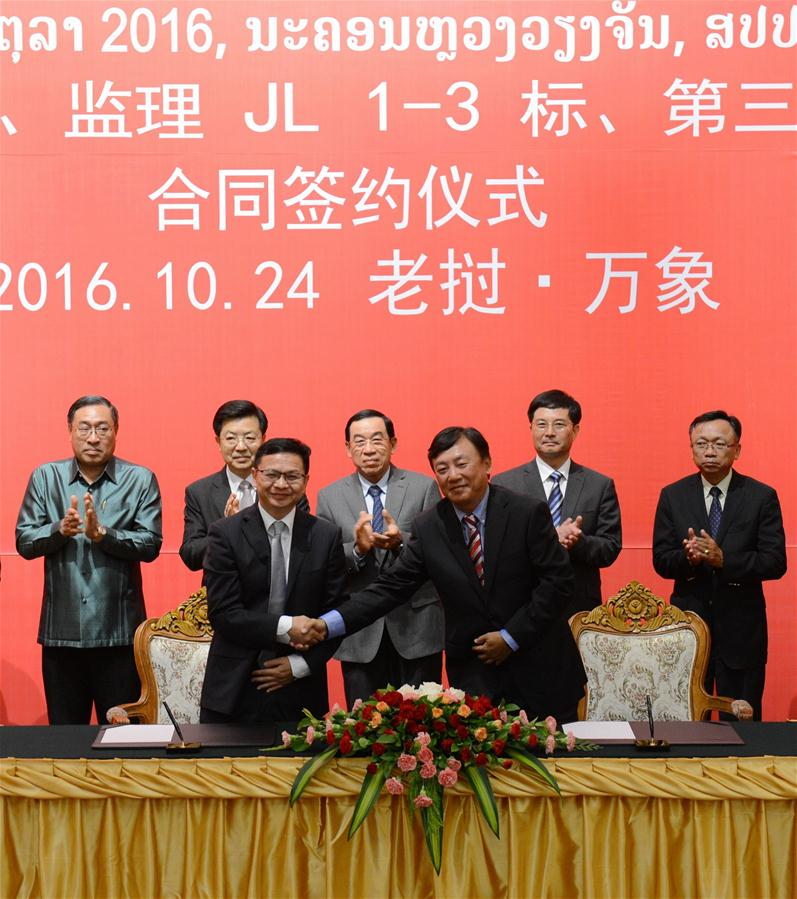 Director General of Laos-China Railway Company Zhao Xiang (R, front) shakes hands with a representative of China