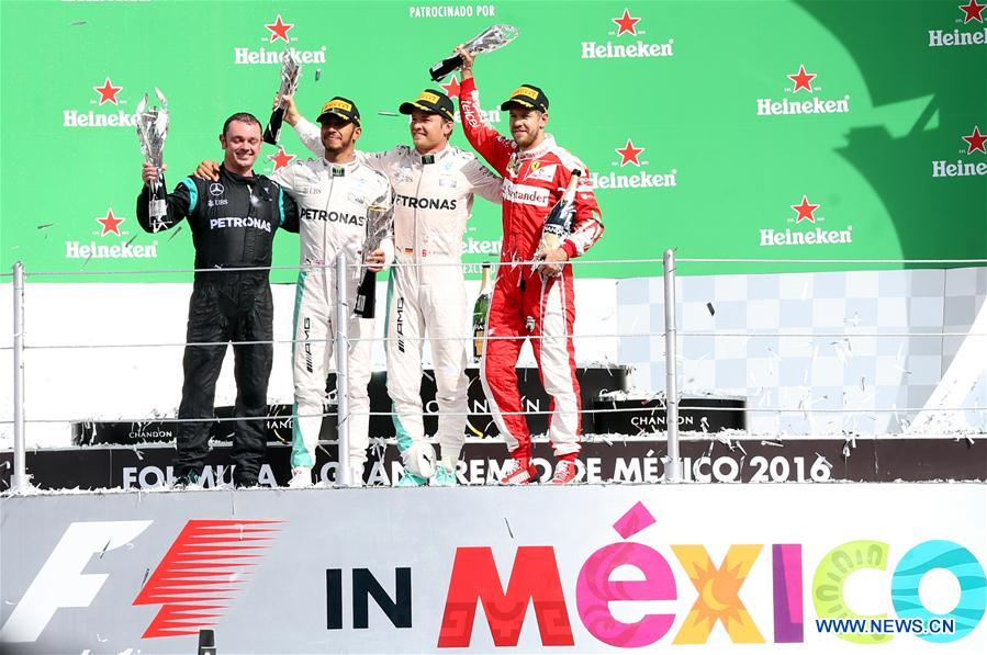 Mercedes team coordinator Tony Walton, Mercedes British driver Lewis Hamilton, Mercedes German driver Nico Rosberg and Ferrari German driver Sebastian Vettel (from L to R) pose on the podium after the Formula One Mexico Grand Prix in Mexico City, capital of Mexico, Oct. 30, 2016. (Xinhua/Str)