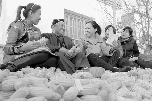 """10月30日,新疆博湖县文化体育广播影视局住村工作组干部来到本布图镇再格森诺尔村村民家中,""""零距离""""解读十八届六中全会精神,让村民及时了解新政策新精神。年 磊摄"""