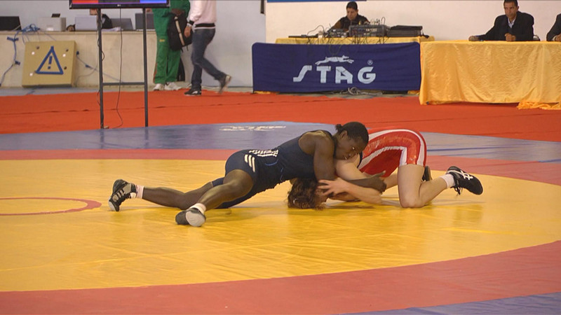 Isabel Sambou, a wrestling champion from Senegal tying down a Tunisian opponent during a competition match.