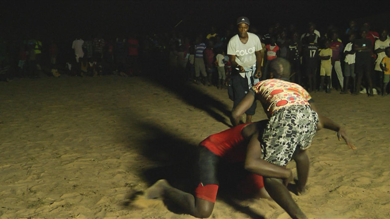Young girls wrestling while their coach Evelyn looks on. Female wrestling is a tradition that has been preserved in Senegal Casamance