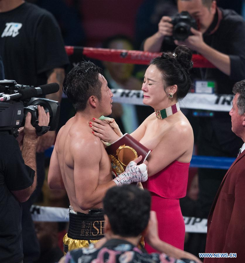 Le Chinois Zou Shiming célèbre avec sa femme Ran Yingying après avoir capturé le titre vacant WBO des poids mouche en dominant aux points le Thaïlandais Prasitsak Phaprom, aux Etats-Unis, le 5 novembre 2016. (Xinhua/Yang Lei)