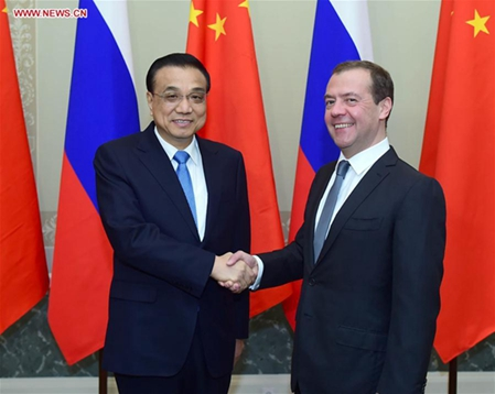 Chinese Premier Li Keqiang (L) shakes hands with his Russian counterpart Dmitry Medvedev at the 21st China-Russia Prime Ministers