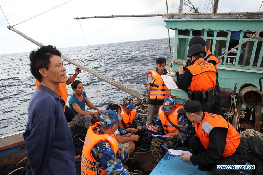 Coast guards from China and Vietnam inspect a Vietnamese fishing boat in a common fishing zone in the Beibu Gulf, Nov. 8, 2016. China and Vietnam concluded a three-day joint patrol mission in a common fishing zone in the Beibu Gulf Wednesday. Coast guards from both sides completed a series of scheduled tasks, including a joint patrol, maritime search and rescue exercise, and examination of fishing boats, amid strong winds and high waves, according to a China Coast Guard (CCG) statement. (Xinhua/Bai Guolong)