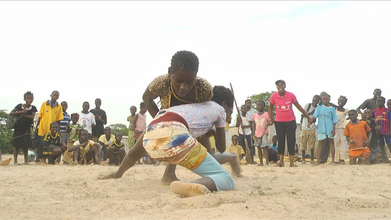 Young aspiring traditional wrestlers taking each other down in a local match held by Evelyn Diatta (in pink top) a wrestling champion in Senegal.