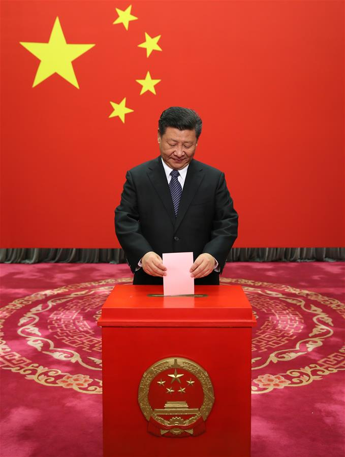Chinese President Xi Jinping casts his ballot at a voting booth to elect new deputies for the local people