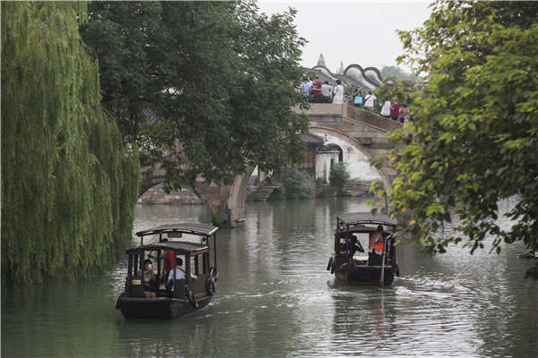 Crisscrossing waterways are now the biggest draw for visitors to Wuzhen, Zhejiang province. Visitors stroll along the banks or hop aboard boats to take in the views. [Photo by Shi Kuihua/For China Daily]