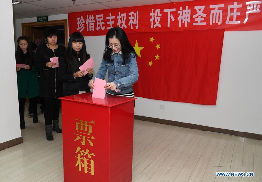 A voter casts her ballot at a voting booth to elect new deputies for the local people