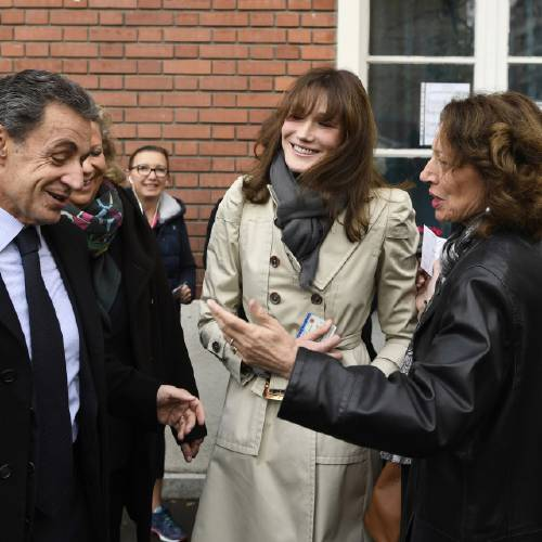 Former French President Nicolas Sarkozy and his wife Carla Bruni-Sarkozy, center, leave the polling station after casting their votes for the conservative primary election, in Paris, Sunday, Nov. 20, 2016. French conservatives are voting in a nationwide primary to choose their nominee for next year