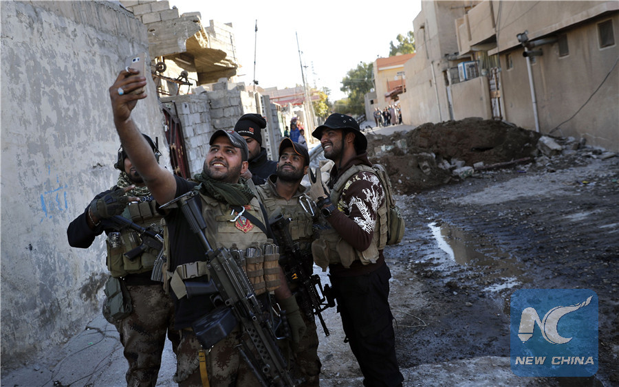 A soldier from the Iraqi Special Forces takes a selfie on a street in the Aden district of Mosul after troops almost entirely retook the area from Islamic State (IS) group jihadists on November 22, 2016. (AFP/Xinhua)