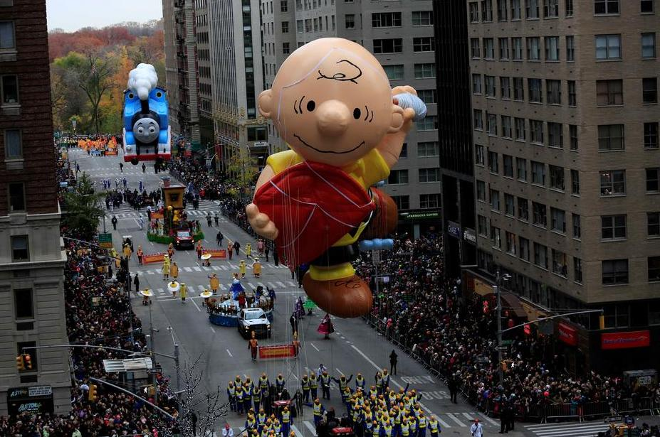 A Charlie Brown giant balloon makes its way down 6th Avenue during the 90th Macy