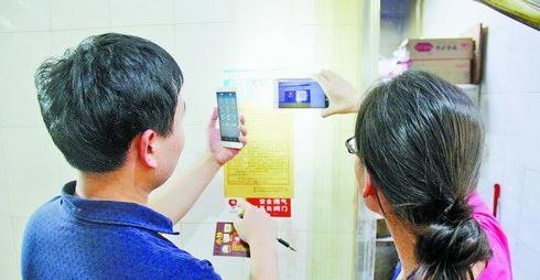 工作人员利用手机App扫描二维码,对餐饮店燃气设施进行动态监管