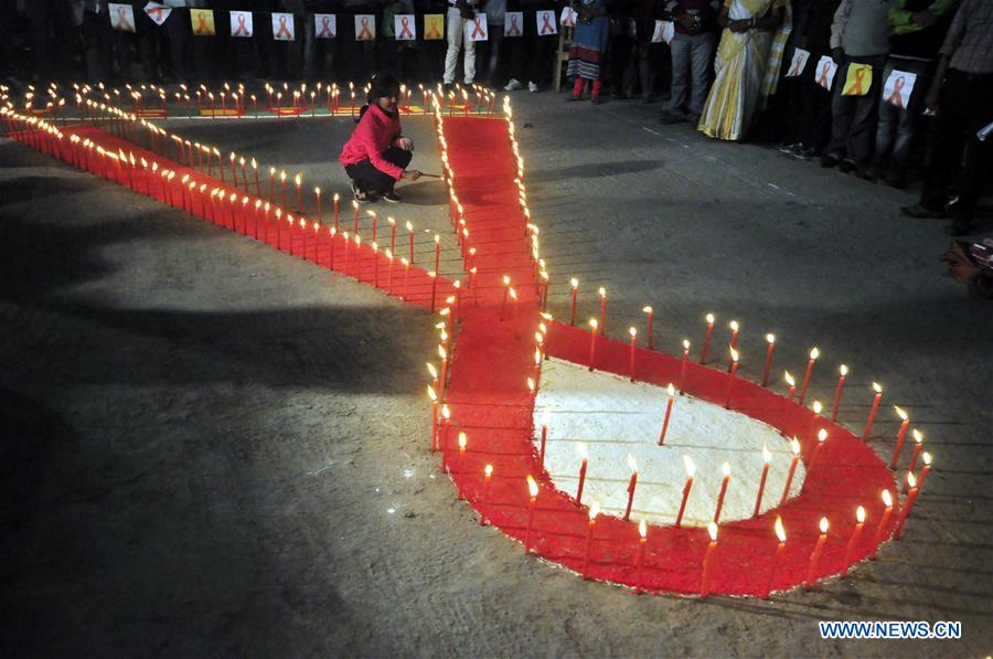People light candles during an AIDS awareness program on the eve of World AIDS Day in Agartala, capital city of Tripura, India, Nov. 30, 2016. World AIDS Day is observed on Dec. 1 every year as millions of people in India are infected with HIV, the AIDS virus, but talking about the disease and sexual health issues in general is still largely taboo. (Xinhua/Stringer)