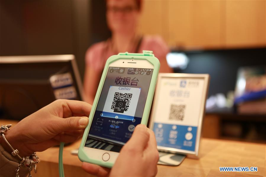 A Chinese tourist pays for souvenirs by scanning Alipay in Rovaniemi, Finland, Dec. 5, 2016. Alipay, the payment service of China