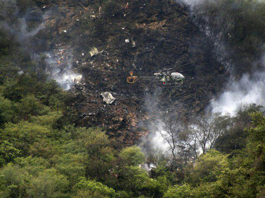 Photo taken on Dec. 7, 2016, shows a helicopter flying over the site of a plane crash in northwest Pakistan